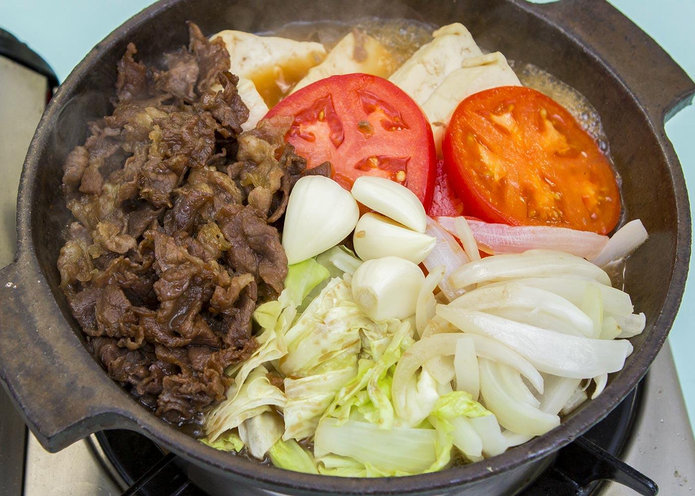 フライパンに【A】を入れ、牛肉を並べ入れ、火にかける。肉の色が変わってきたら返して片側に寄せ、豆腐、玉ねぎ、キャベツ、トマトを並べて入れる。
