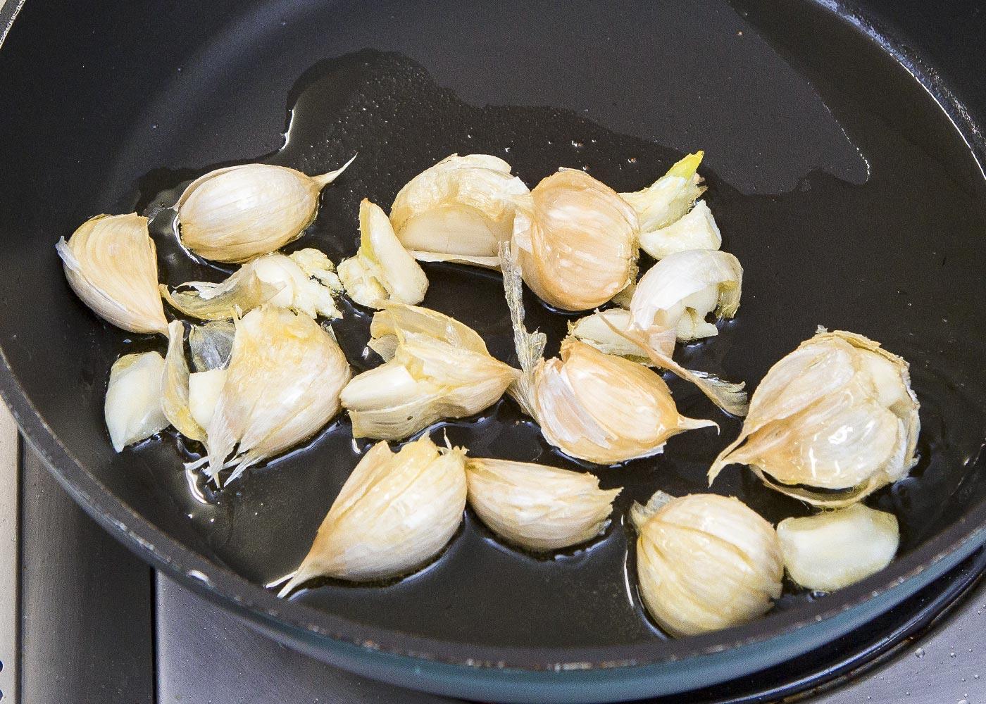 鍋に皮付きのにんにくとオリーブ油を入れ、弱火にかけ、にんにくの上下を返しながら火を通す。