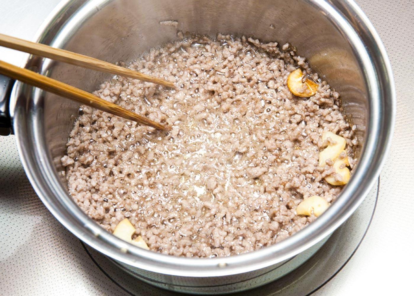 鍋にごま油とにんにくを入れ、弱火にかける。いい香りが立ってきたら、豚ひき肉を加え、強火で炒める。