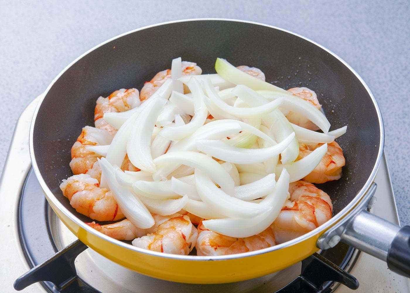 フライパンを温め、サラダ油を流し、えびを並べ入れ、玉ねぎを加える。